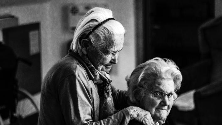 Äldre kvinna står bakom och håller om annan äldre kvinna.