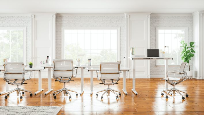 Kontorsrum med flera höj- och sänkbara skrivbord.